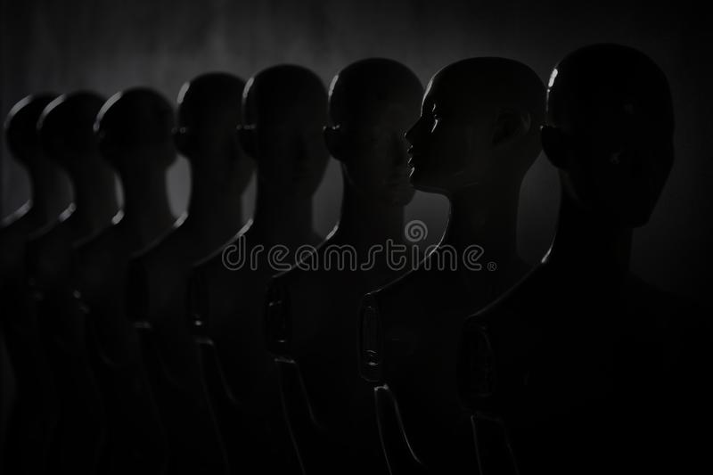 Dark Picture of Plastic Woman Figurines Standing in The Line stock photo