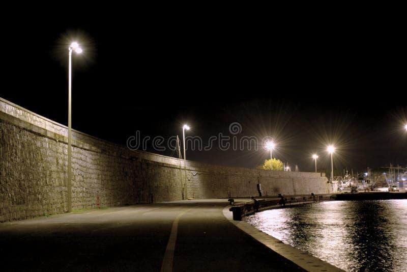 Dark pier sidewalks at night in the city of Terracina, Italy.  royalty free stock photos