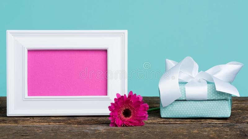 Dark pink gerbera on a table with empty picture frame and a present. Happy Mother`s Day background. royalty free stock photos