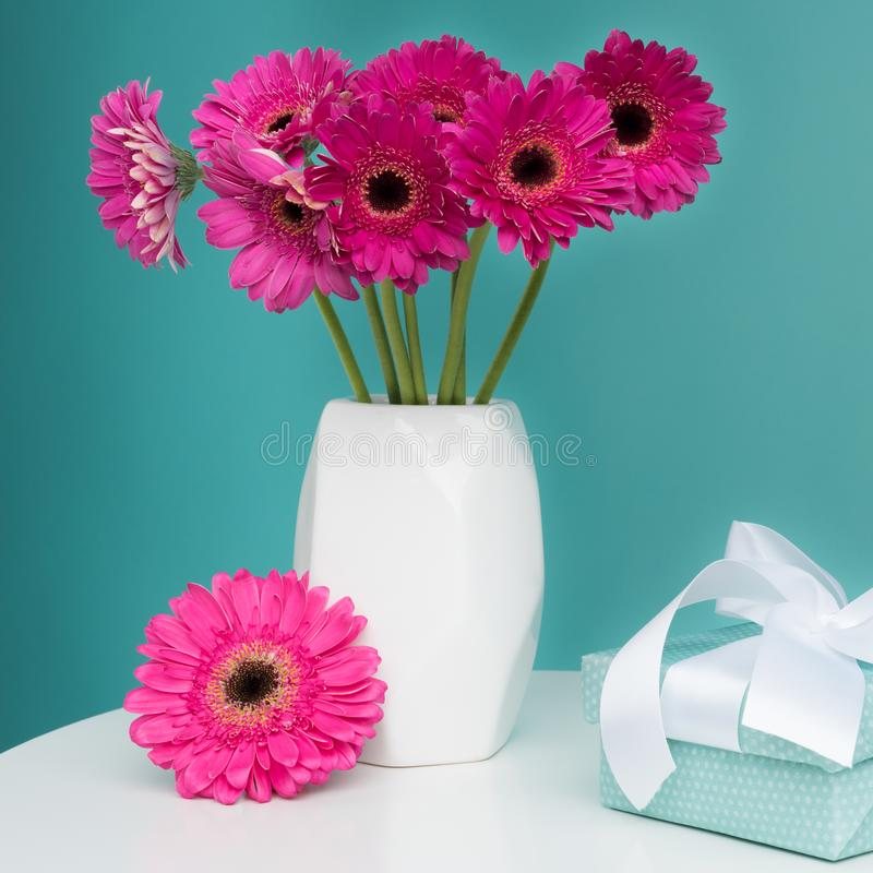 Dark pink gerberas in a vase on a table with beautiful present. Happy Mother`s Day, Women`s Day, Valentine`s Day or Birthday. Happy Mother`s Day, Women`s Day stock photos