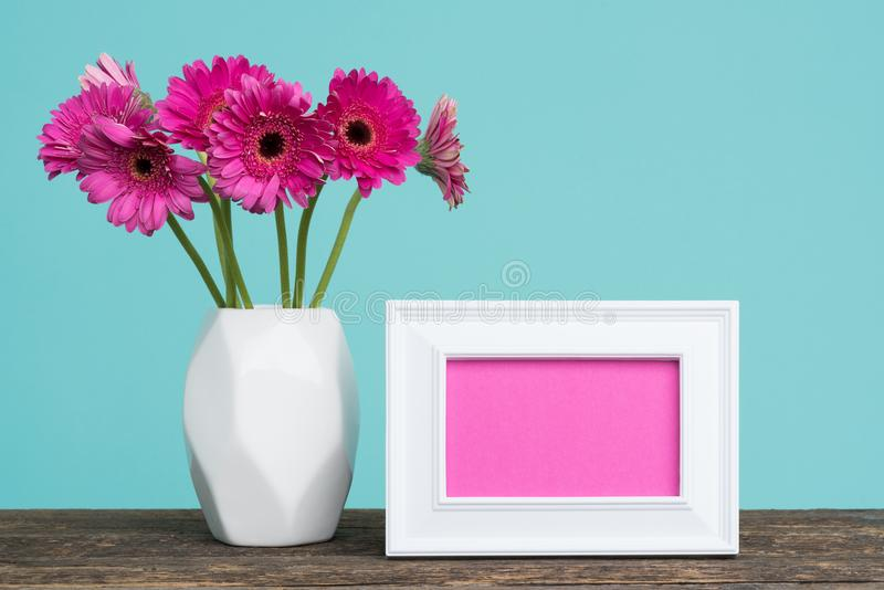 Dark pink gerberas in a vase on a table with empty picture frame greeting card. stock image