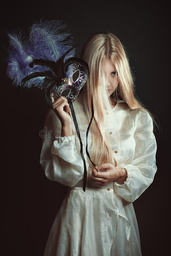 Dark portrait of woman with purple mask royalty free stock photos