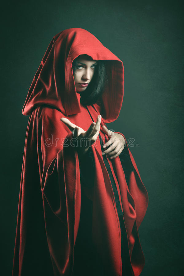 Dark portrait of a beautiful woman with red cloak royalty free stock image