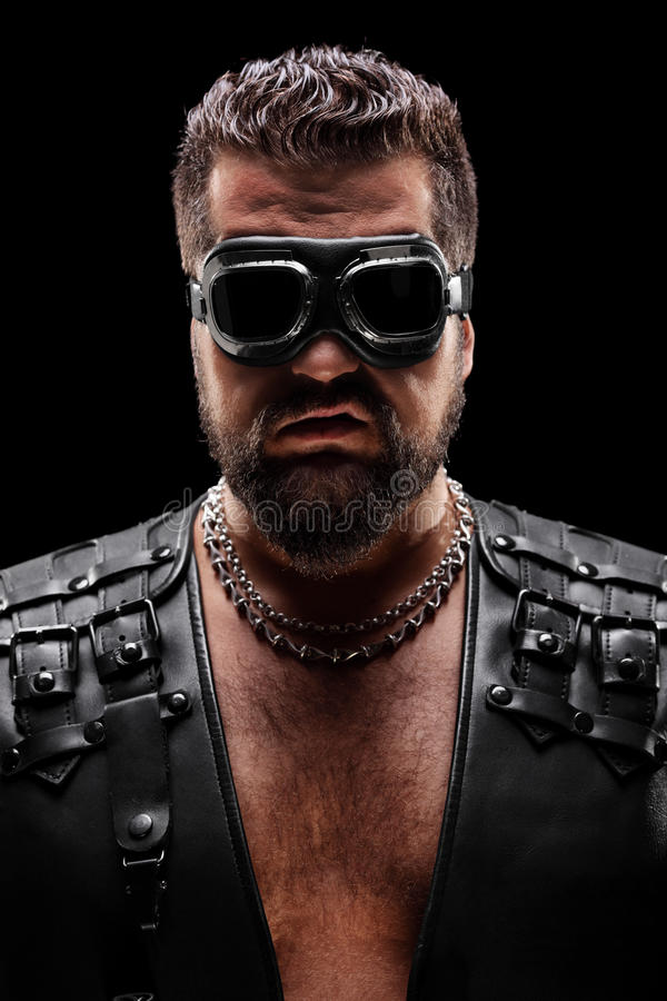 Dark portrait of a male biker with goggles royalty free stock photo