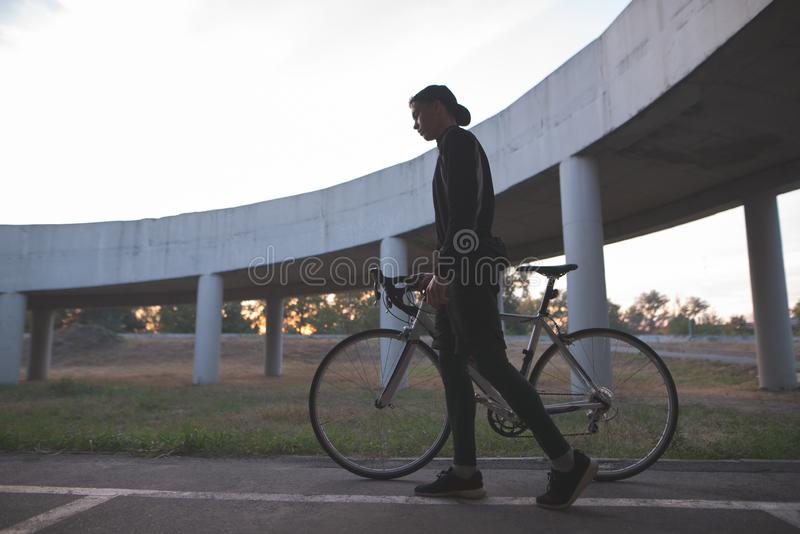 Dark portrait of a rider. Silhouette of a cyclist with a bicycle on the background of a bridge royalty free stock photography
