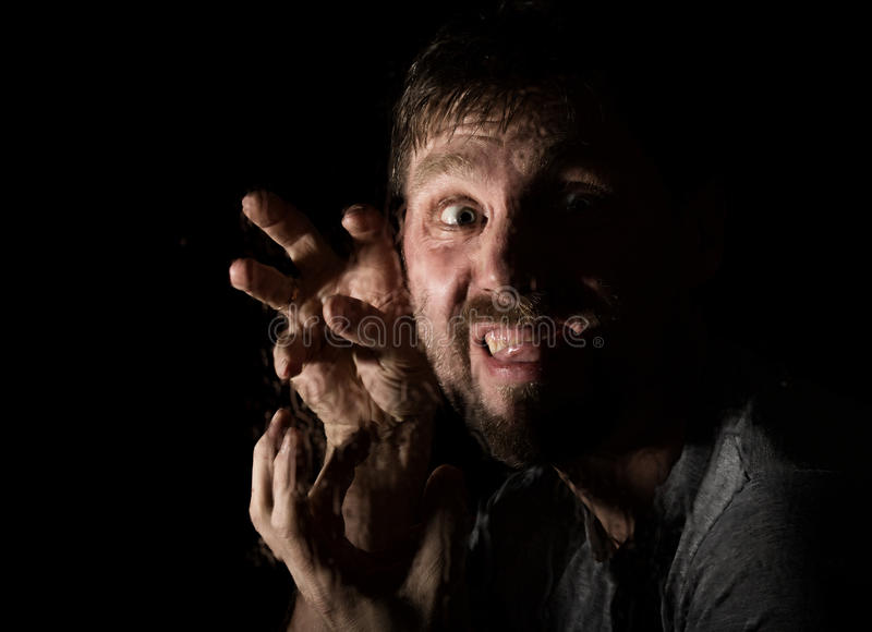 Dark portrait of scary bearded man with smirk, expresses different emotions. Drops of water on a glass, hand and male royalty free stock image