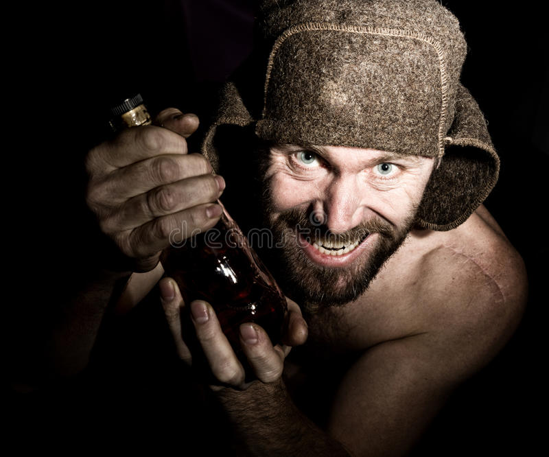 Dark portrait of scary evil sinister bearded man with smirk, holding a bottle of cognac. strange Russian man with a royalty free stock photos