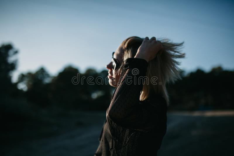 Dark portrait of woman in profile while touching her hair with backlighting royalty free stock photos