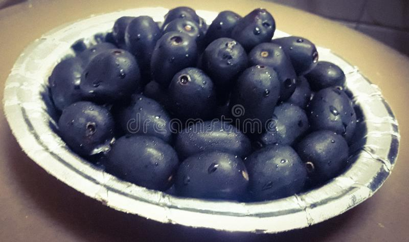 The dark purple edible berry called as Jamun served on a silver coloured paper plate stock photo