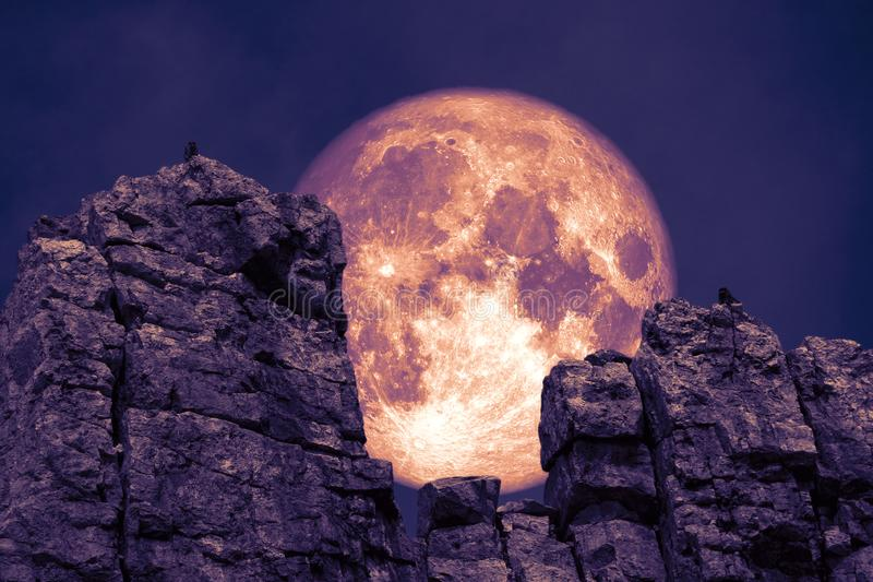 dark purple moon back over stone and monsters on rock between cliff royalty free stock images