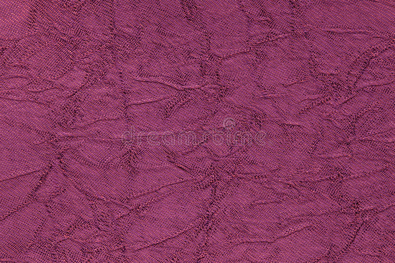 Dark purple wavy background from a textile material. Fabric with fold texture closeup. Creased shiny magenta cloth royalty free stock images