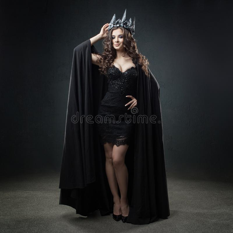 The dark Queen. Attractive and young woman in long black cloak and crown. royalty free stock image