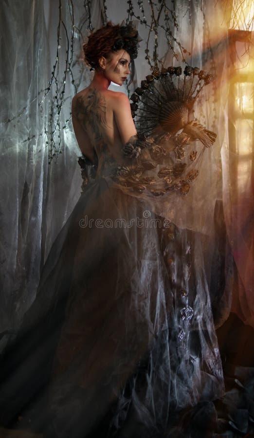 Dark queen in black fantasy costume. On dark gothic background royalty free stock photos