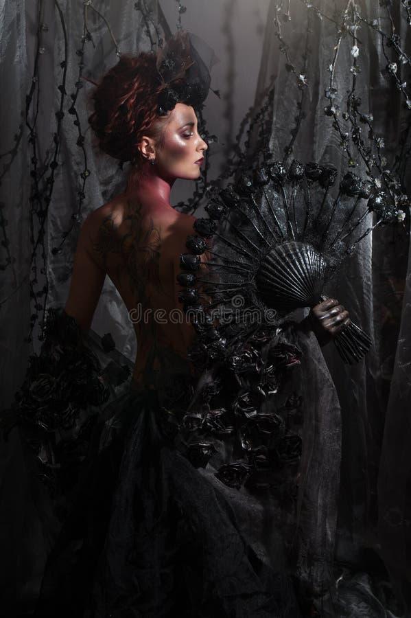 Dark queen in black fantasy costume. On dark gothic background stock images