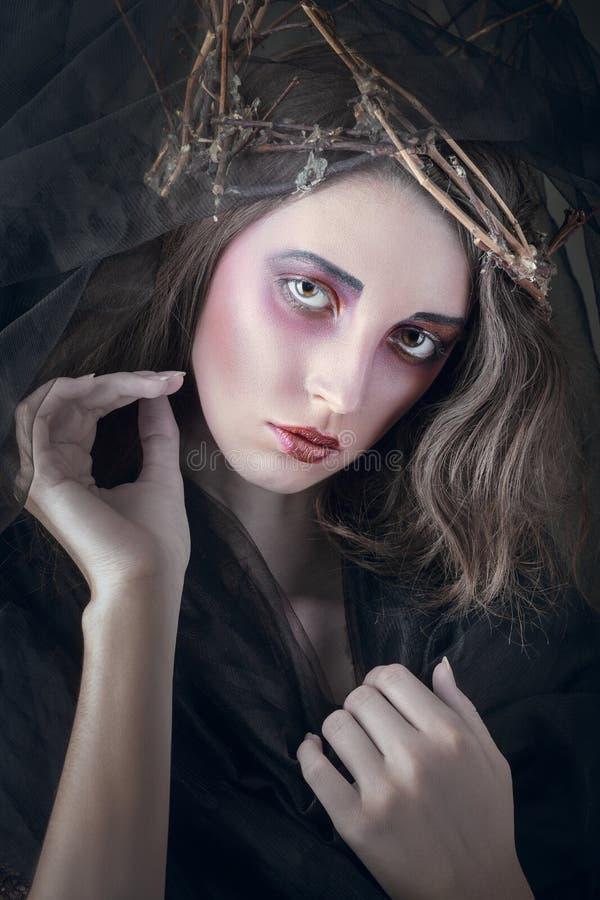 Dark queen makeup. Sad beautiful young woman with dark queen makeup stock photos