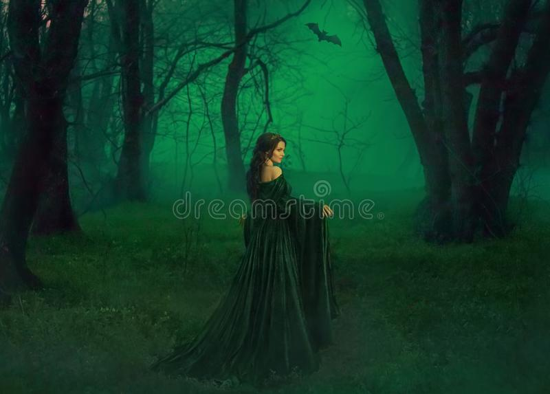 Dark queen of otherworldly forces leads into realm of dead souls. bloody vampire in long velor emerald dress lures into. Her lair, lost pretty princess with stock photo