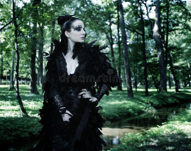 Dark Queen in park. Fantasy black dress royalty free stock photography