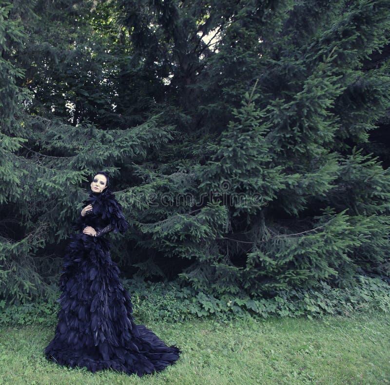 Dark Queen in park. Fantasy black dress royalty free stock images