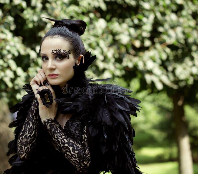 Dark Queen in park. Fantasy black dress stock photography