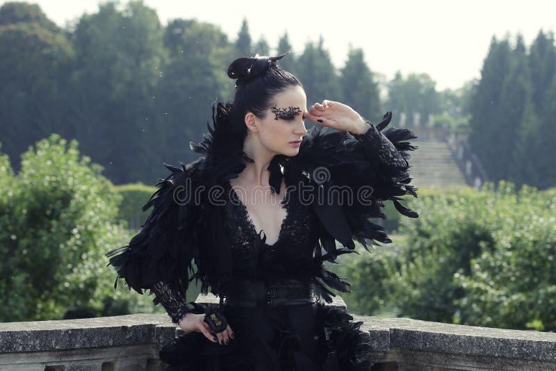 Dark Queen in park. Fantasy black dress royalty free stock photo