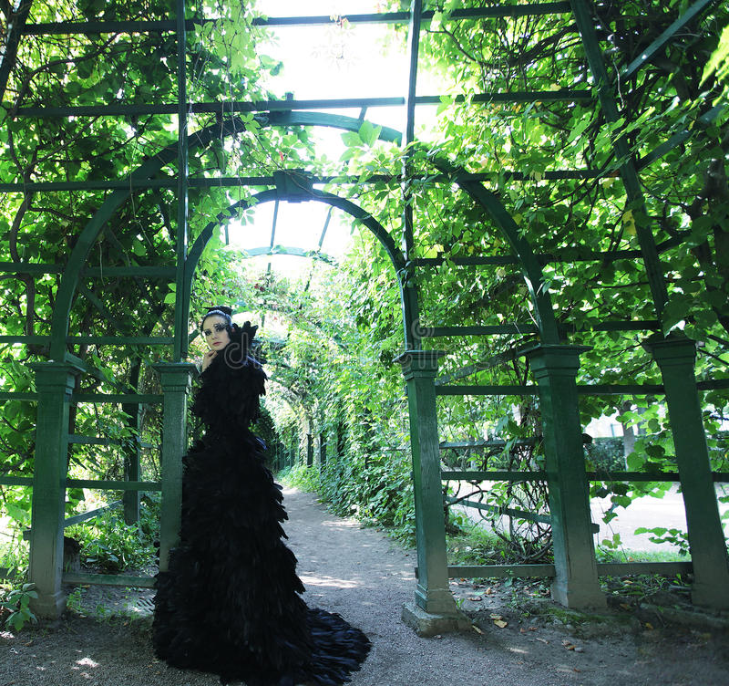 Dark Queen in park. Fantasy black dress stock images