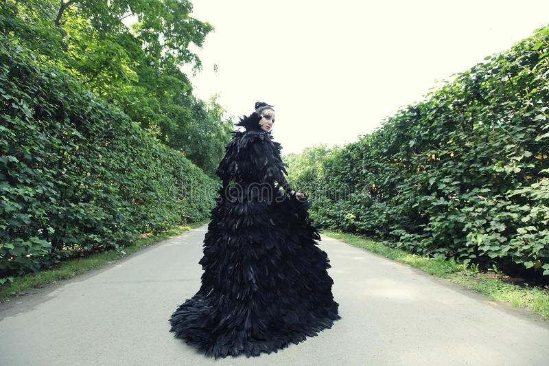 Dark Queen in park. Fantasy black dress stock image