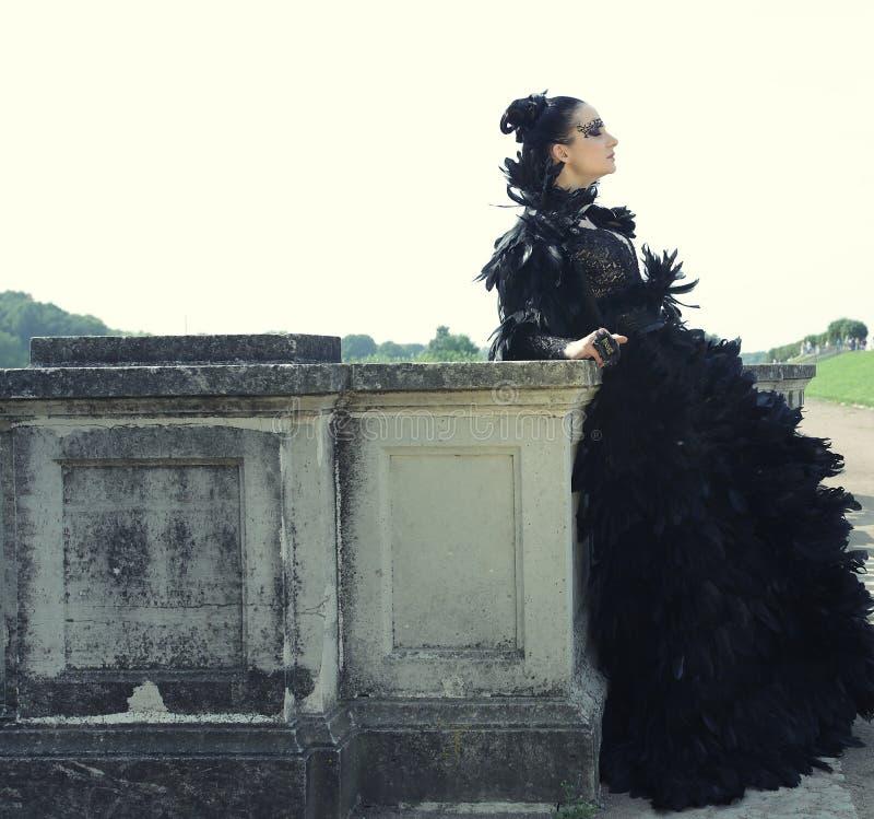 Dark Queen in park. Fantasy black dress stock photo