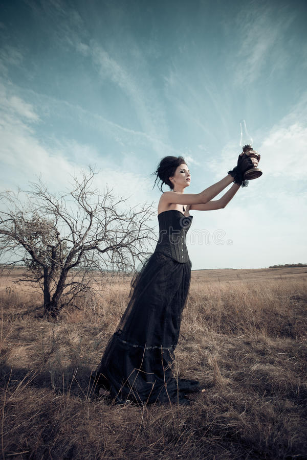 Dark Queen in park. Fantasy black dress. royalty free stock images