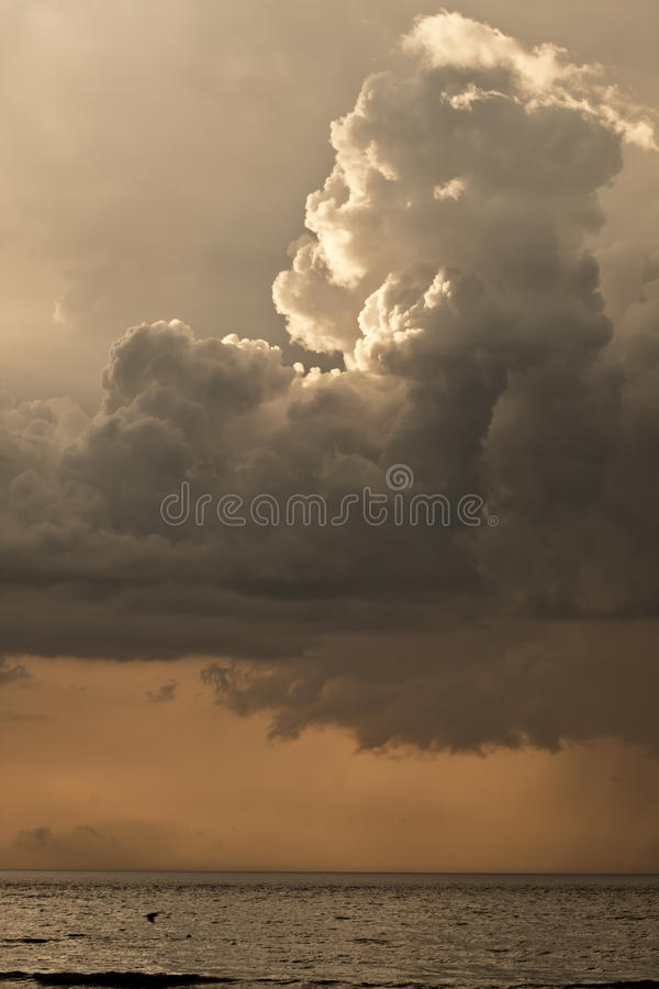 Dark rain clouds. Dark storm clouds with sun ray over the sea stock photography