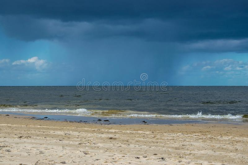 Dark rain clouds above the Baltic sea. Raining stock image