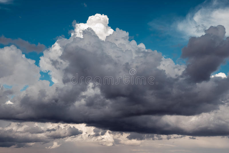 Dark rain clouds on a blue sky for background.  stock image