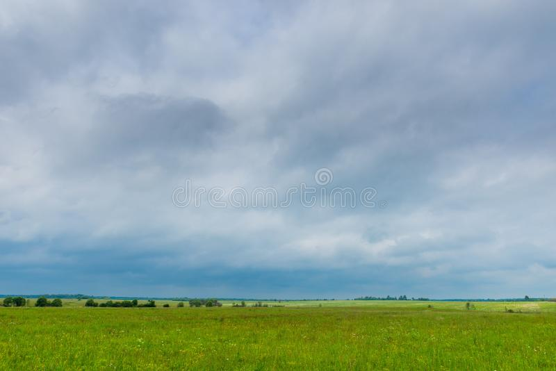 Dark rainy clouds hang on a green spring field stock photos