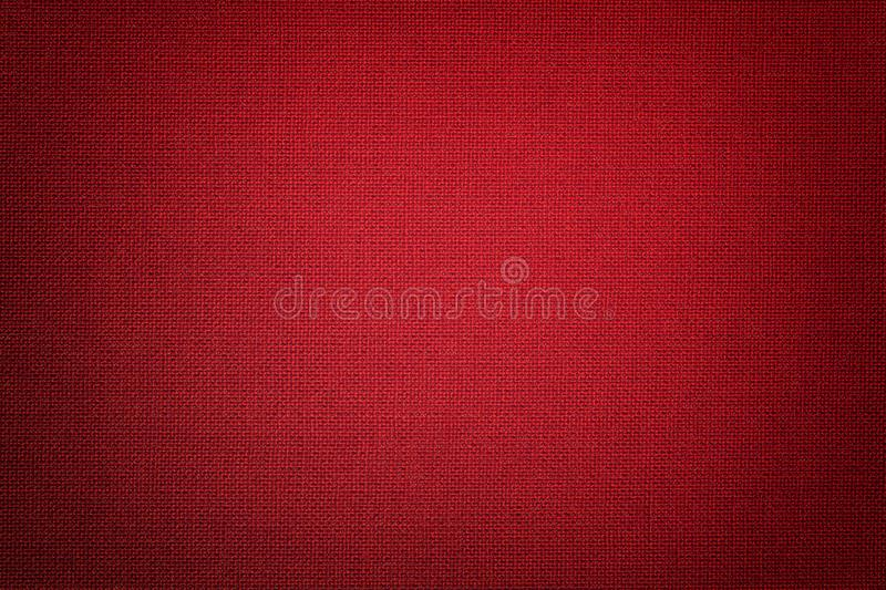Dark red background from a textile material with wicker pattern, closeup. Structure of the wine fabric with texture. Cloth backdrop ruby with vignette royalty free stock photos