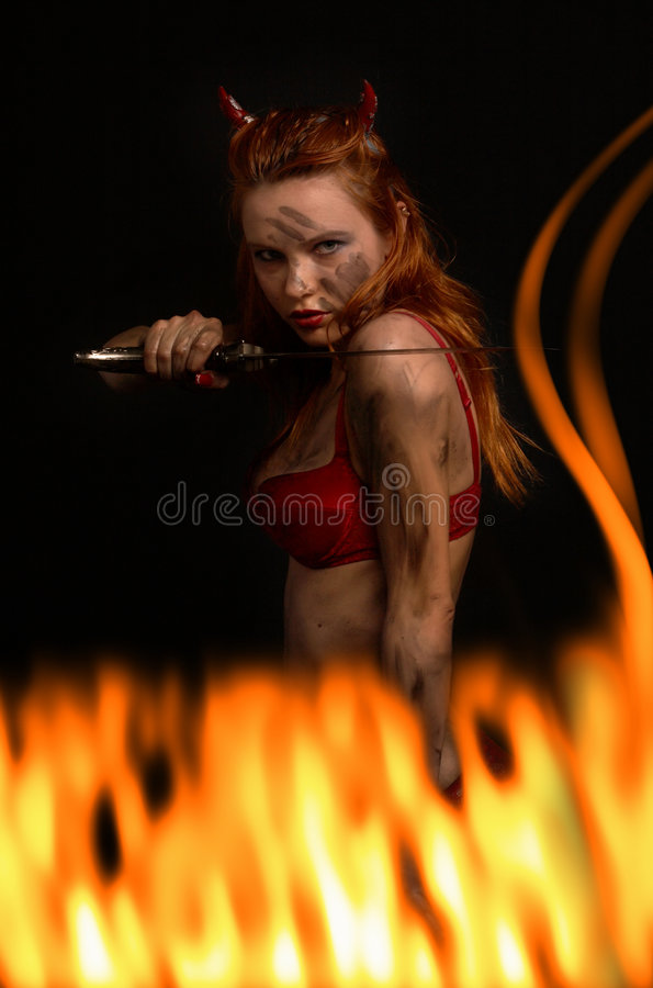 Dark red devil girl with a kni. Fe in burning fire stock photos
