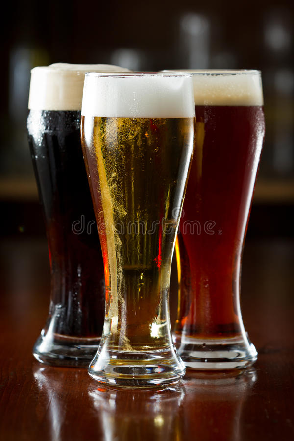 Dark, red and light beer. Served on a dark bar stock image