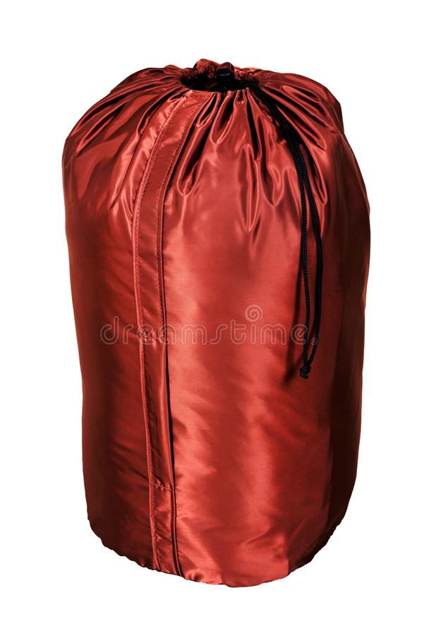 Dark red shiny tourist sleeping bag, isolated on white background, designed for hiking tours and tents stock photography