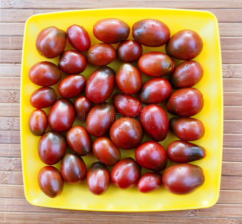 Dark red tomatoes on a yellow plate stock photo