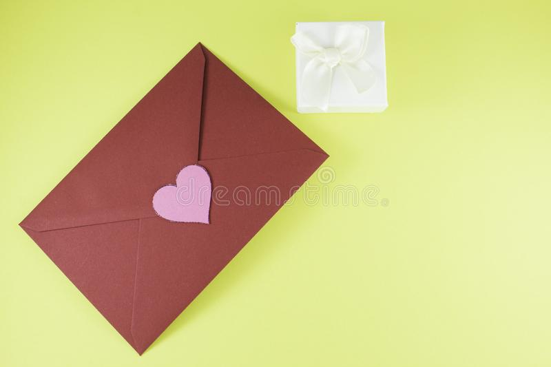 Dark red triangle envelope with large pink heart on yellow background Valentine`s day. Dark red triangle envelope with large pink heart on yellow background with stock photography