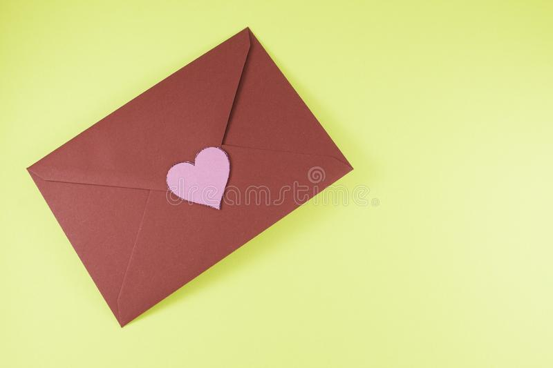Dark red triangle envelope with large pink heart on yellow background Valentine`s day. Or festive concept Letter or invitation inside closed envelope Minimalist stock image