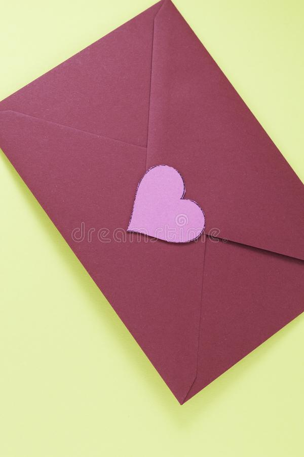 Dark red triangle envelope with large pink heart on yellow background Valentine`s day or festive concept Letter or invitation royalty free stock photo