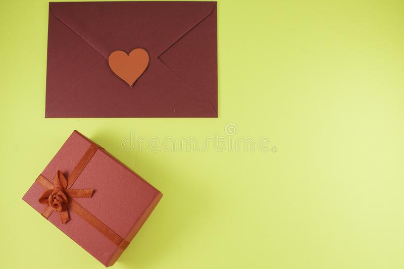 Dark red triangle envelope with large red heart on yellow background with gift box Valentine`s day. Or festive concept Letter or invitation inside closed stock images
