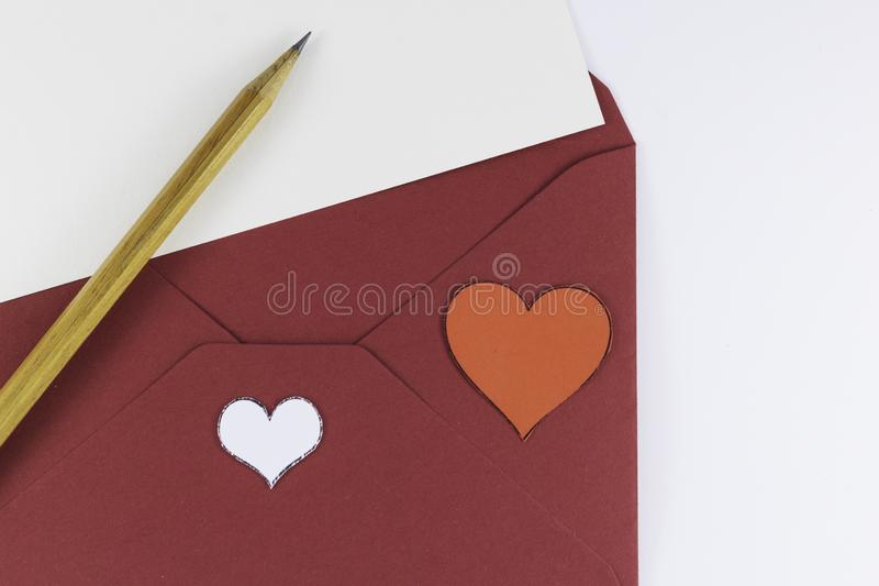 Dark red triangle envelope opened with letter and two hearts and wooden pencil near on white background Valentine`s. Day or festive concept Letter or invitation royalty free stock image