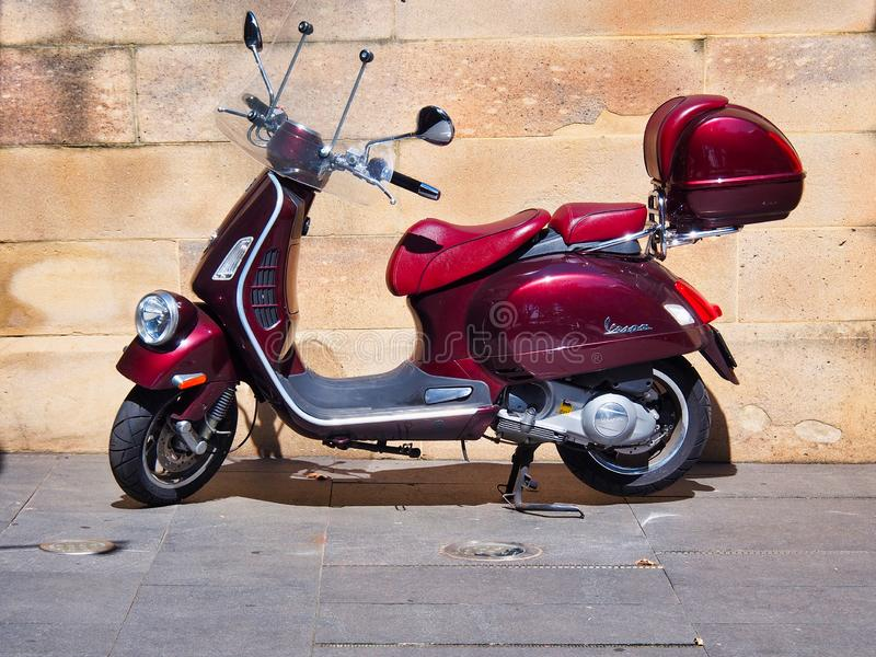 Dark Red Vespa Scooter parked Near Old Sandstone Wall royalty free stock photos