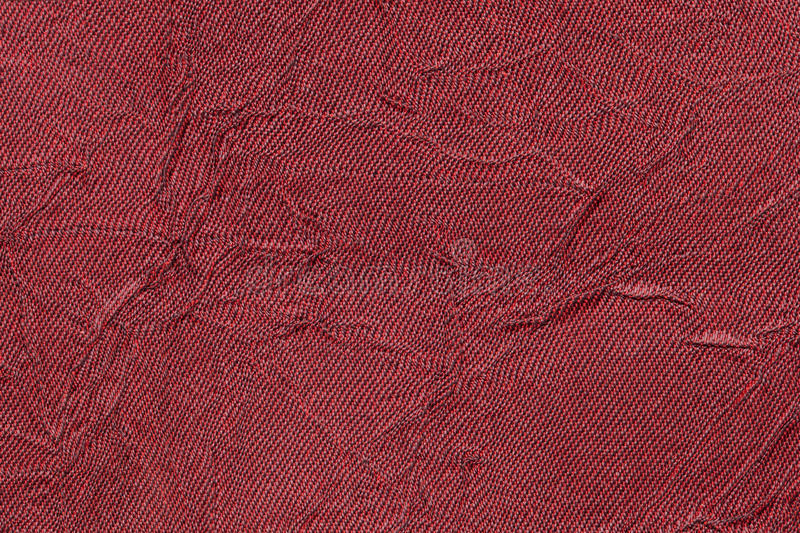 Dark red wavy background from a textile material. Fabric with fold texture closeup. Creased shiny maroon cloth stock image
