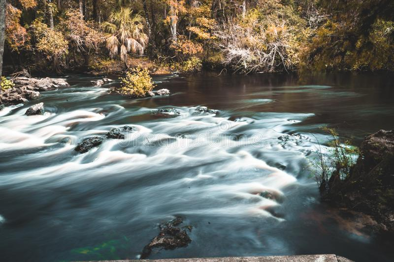 Dark river with rapids and rocks. Long exposure morning at park stock photography