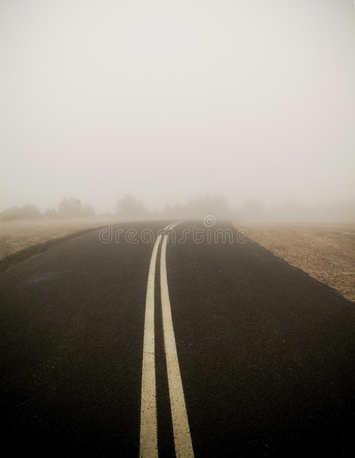 Dark Road in Fog. Dark road with double lines disappears into very thick winter fog royalty free stock photo