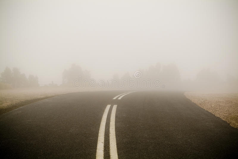 Dark Road in Fog. Dark road with double lines disappears into very thick winter fog stock image