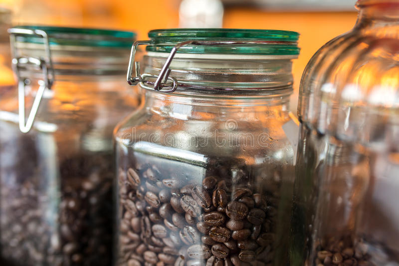 Dark roasted coffee beans in a jar of glass royalty free stock photos