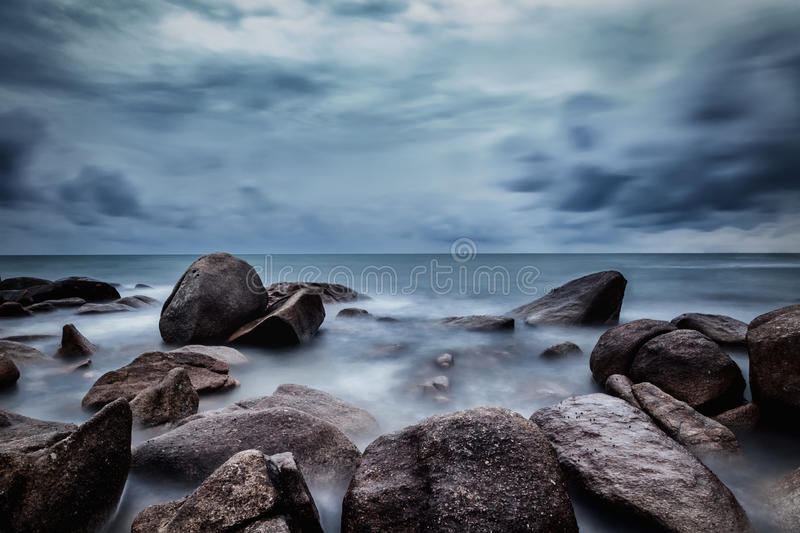 Dark rocks in a blue ocean under cloudy sky in a bad weather., L. Ong exposure photography stock photo