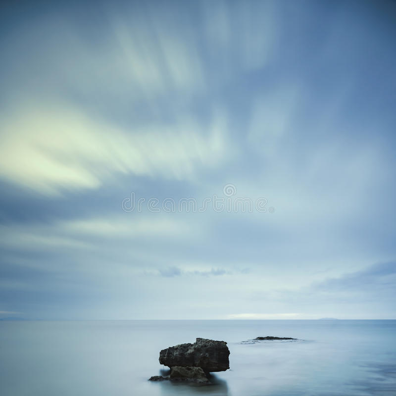 Dark rocks in a blue ocean under cloudy sky in a bad weather. stock images